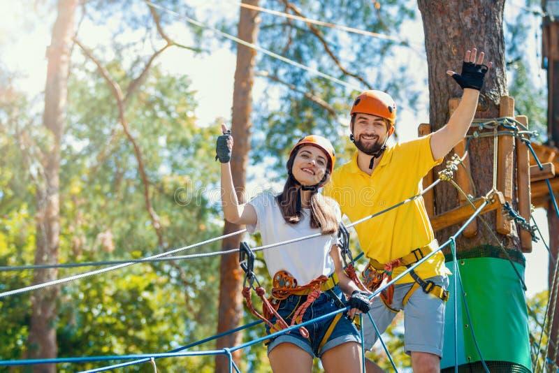 Het paar in liefde geniet van actieve vrije tijd in extreem kabelpark royalty-vrije stock afbeeldingen