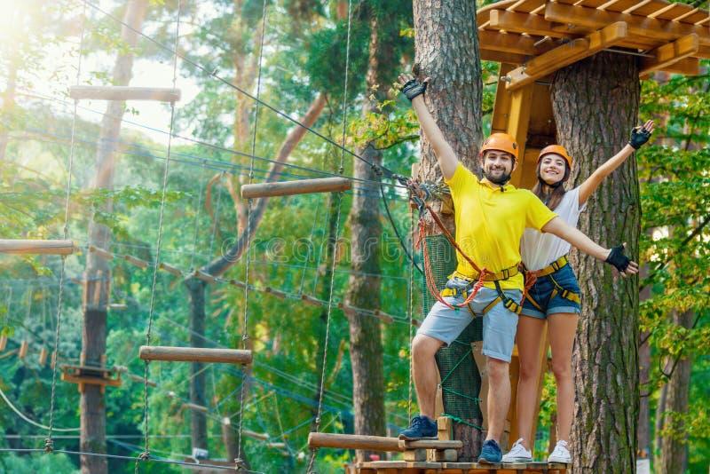 Het paar in liefde geniet van actieve vrije tijd in extreem kabelpark stock foto