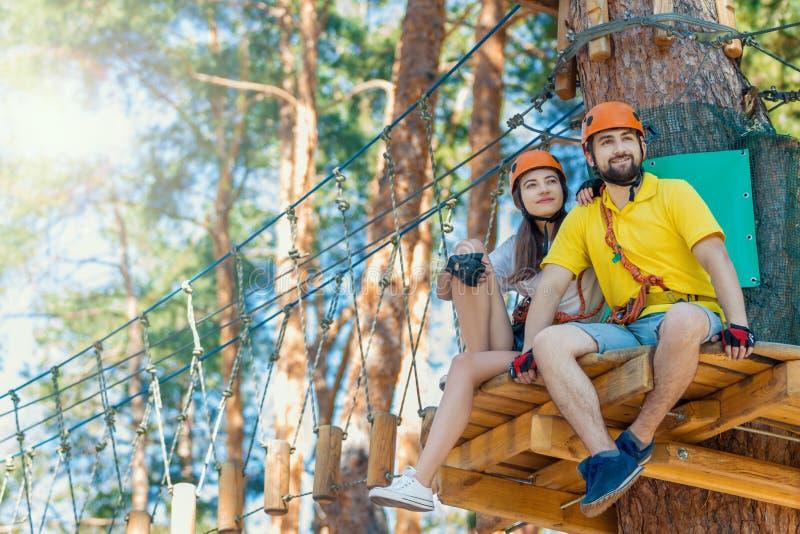 Het paar in liefde geniet van actieve vrije tijd in extreem kabelpark stock afbeelding