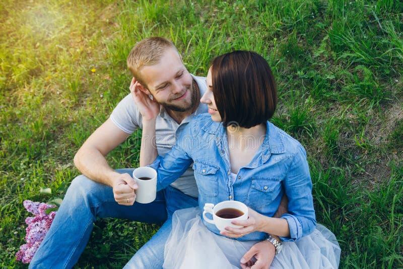 Het paar in liefde heeft een rust in de boomgaard van de zomerapple royalty-vrije stock afbeeldingen