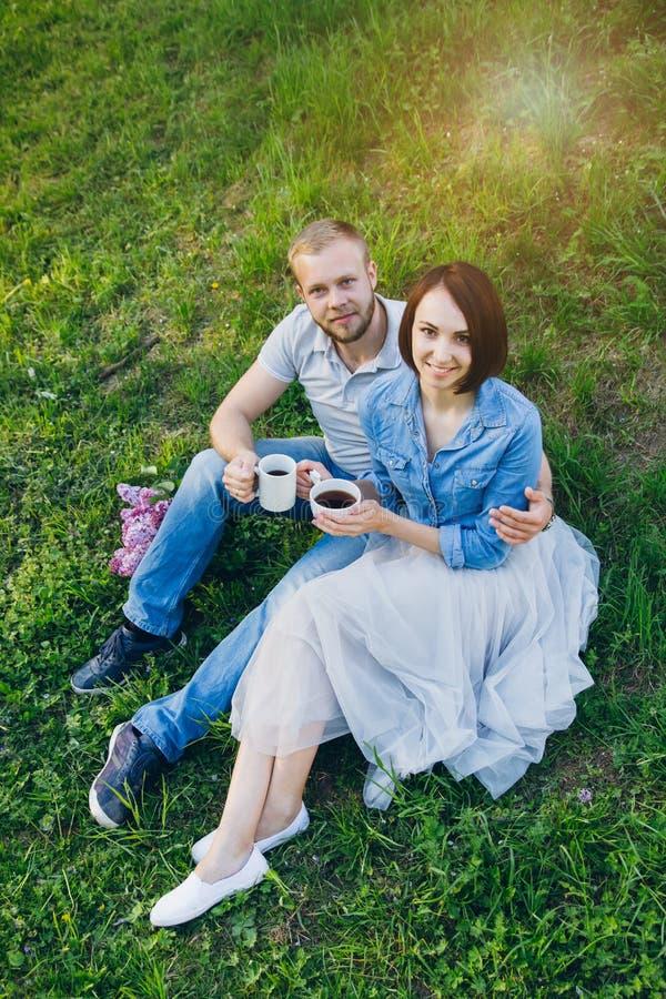 Het paar in liefde heeft een rust in de boomgaard van de zomerapple royalty-vrije stock afbeelding
