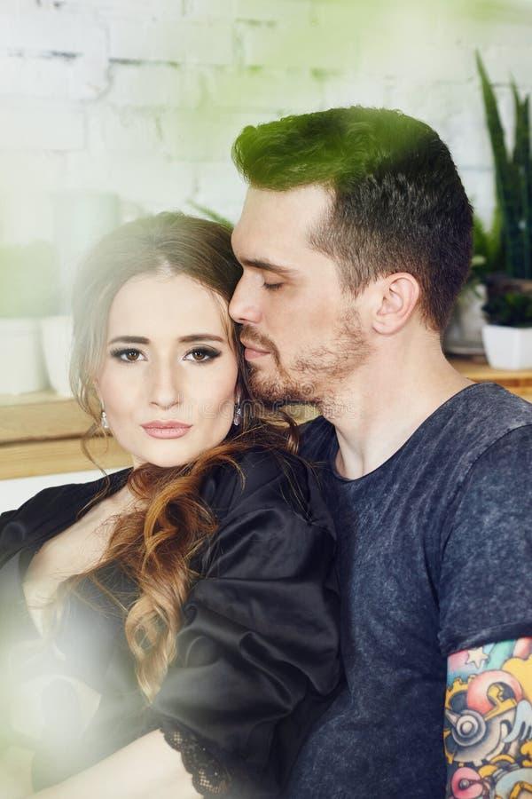 Het paar in liefde heeft Ontbijt vroeg in de keuken in de ochtend Omhelzingen en kussen, sexy meisje in Badjas en mens Weekendoch stock foto