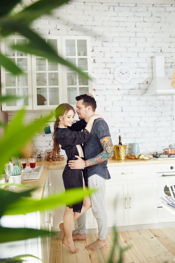 Het paar in liefde heeft Ontbijt vroeg in de keuken in de ochtend Omhelzingen en kussen, sexy meisje in Badjas en mens Weekendoch stock afbeeldingen