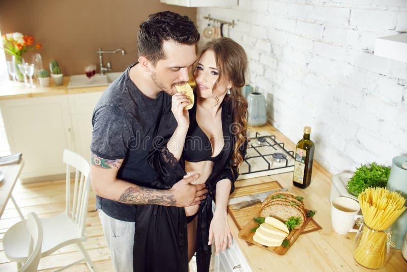 Het paar in liefde heeft Ontbijt vroeg in de keuken in de ochtend Omhelzingen en kussen, sexy meisje in Badjas en mens Weekendoch stock afbeelding