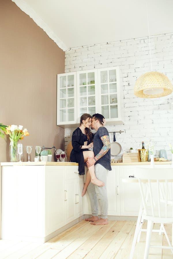 Het paar in liefde heeft Ontbijt vroeg in de keuken in de ochtend Omhelzingen en kussen, sexy meisje in Badjas en mens Weekendoch royalty-vrije stock fotografie
