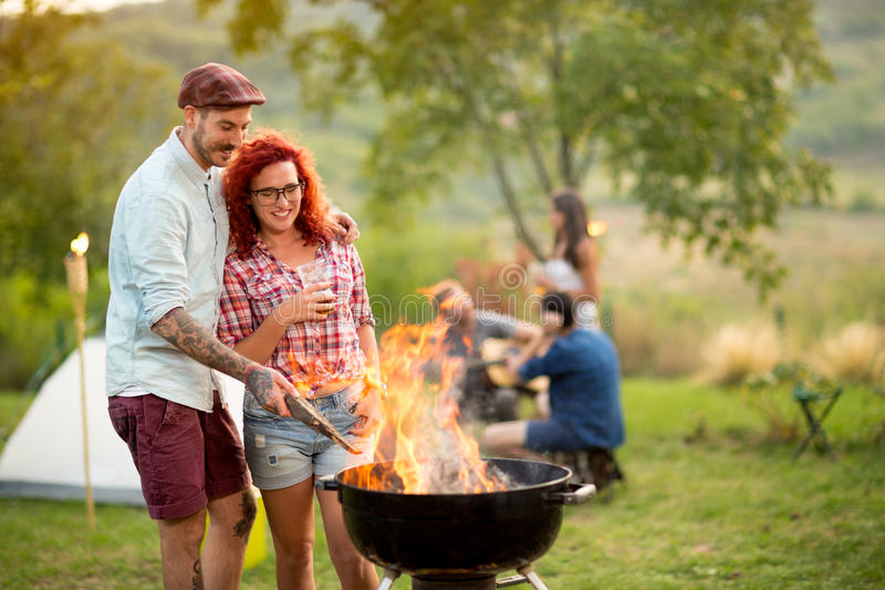 Het paar in liefde het drinken bier en bereidt grillbrand voor stock foto's