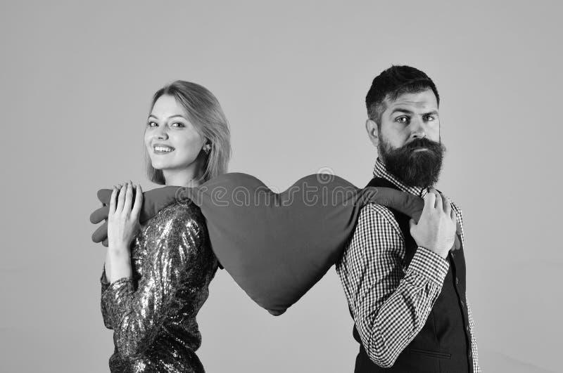 Het paar in liefde houdt groot hart op roze achtergrond Het meisje en de gebaarde mens met het glimlachen gezichten verdelen stuk stock afbeelding