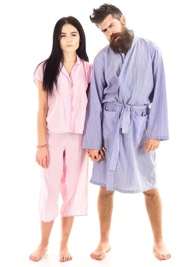 Het paar in liefde houdt handen, op witte achtergrond worden geïsoleerd die Jong slaperig paar in liefde geknuffel zacht in pyjam stock fotografie