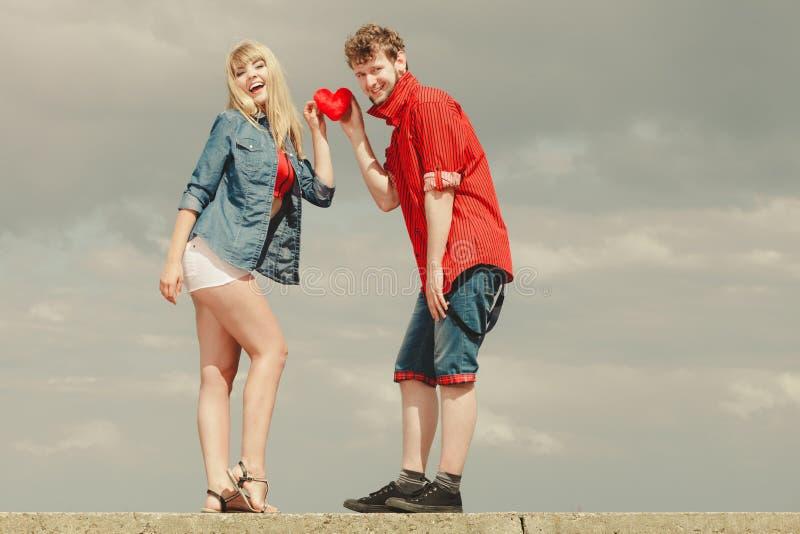 Het paar in liefde houdt rood hart openlucht stock fotografie