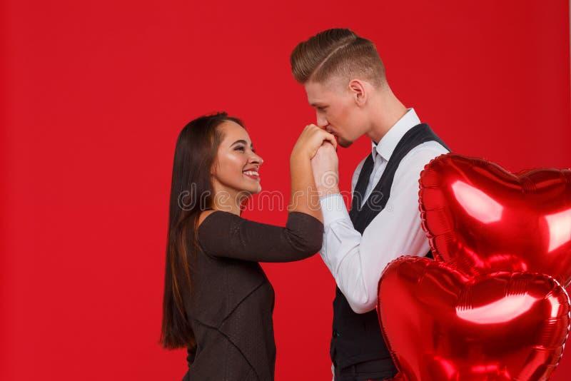 Het paar in liefde, kerel kust een meisjes` s hand, naast ballen in de vorm van een hart Rode achtergrond stock afbeelding