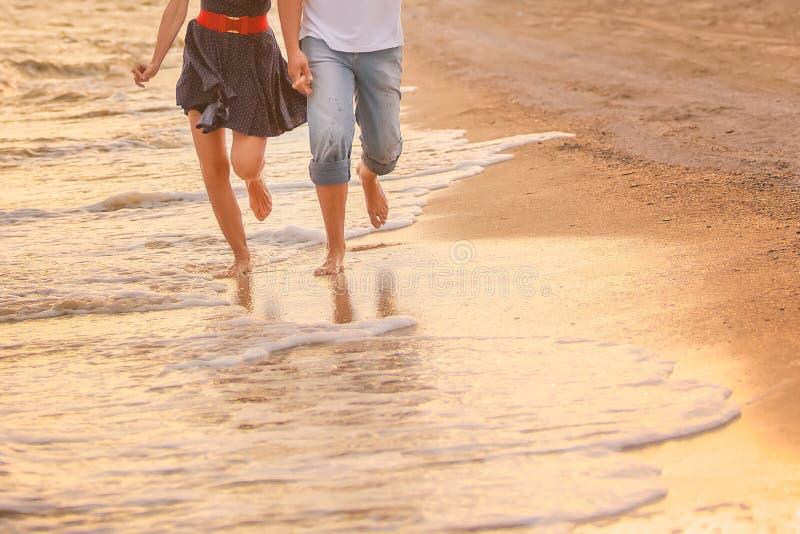 Het paar in liefde loopt blootvoets op het overzees langs de branding bij zonsondergang wittebroodsweken, valentijnskaart, geluk  royalty-vrije stock afbeeldingen