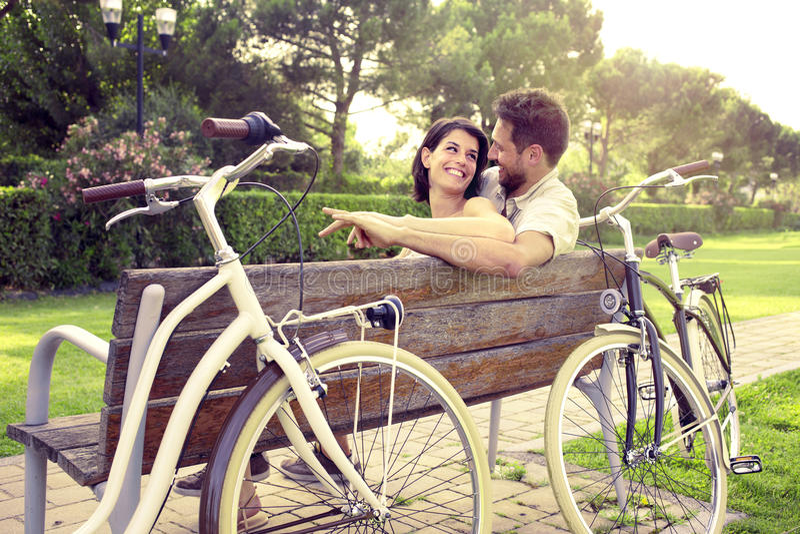 Het paar in liefde sitted togheter op een bank met fietsen naast stock foto's