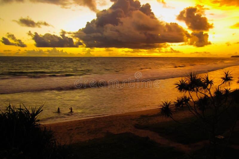 Het paar in liefde wordt gefotografeerd in de oceaan bij zonsondergang stock foto