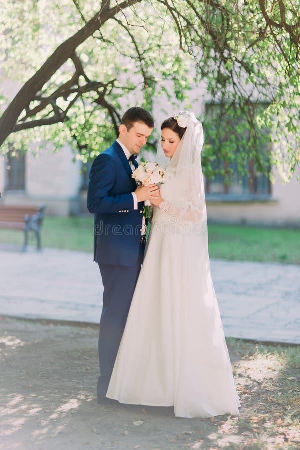 Het paar in liefdebruid en de bruidegom bekijken in openlucht bruids boeket van witte rozen royalty-vrije stock foto