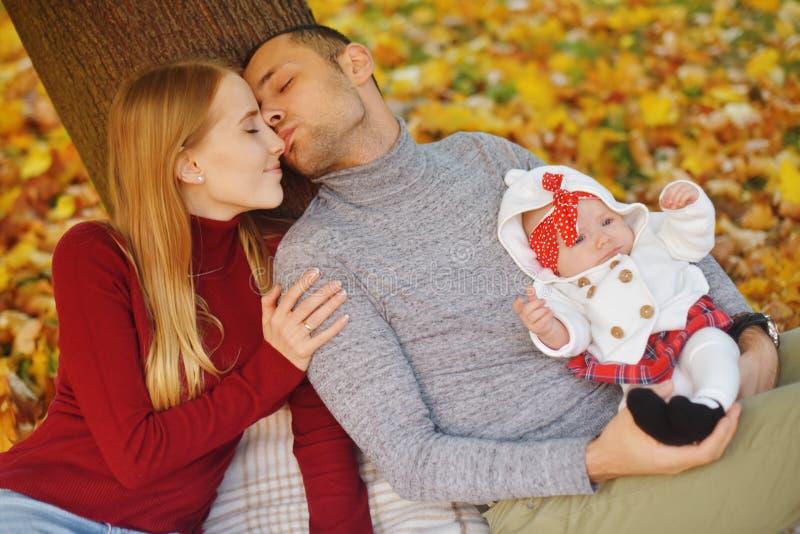 Het paar in liefdezitting op de herfst gevallen bladeren in een park, zit dichtbij een boom, genietend van een mooie de herfstdag royalty-vrije stock foto