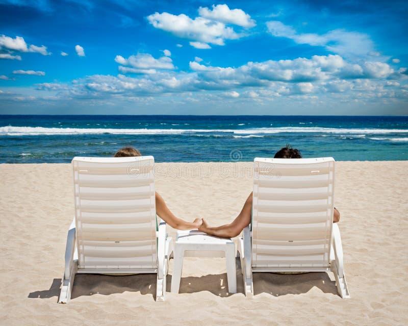 Het paar in ligstoelen het houden overhandigt dichtbij oceaan royalty-vrije stock afbeelding