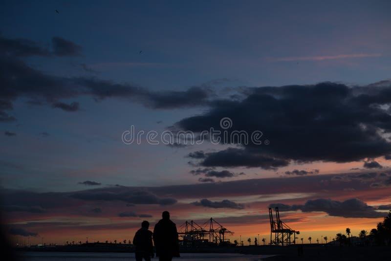 Het paar loopt langs het strand tijdens zonsondergang stock foto's