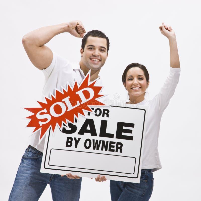 Het paar met huis FSBO verkocht teken. royalty-vrije stock afbeeldingen