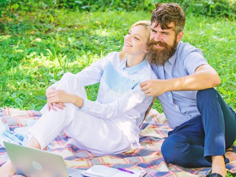 Het paar met laptop ontspant natuurlijk milieu Ontspannen de paar gebaarde man en de blondevrouw aard terwijl op groen gras zit stock afbeeldingen