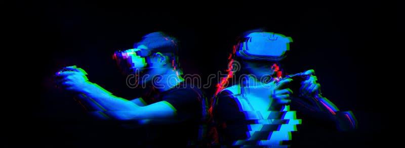 Het paar met virtuele werkelijkheidshoofdtelefoon speelt spel Beeld met glitch effect stock afbeeldingen
