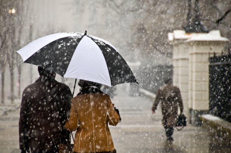 Het paar neemt een romantische gang in de sneeuw stock foto's