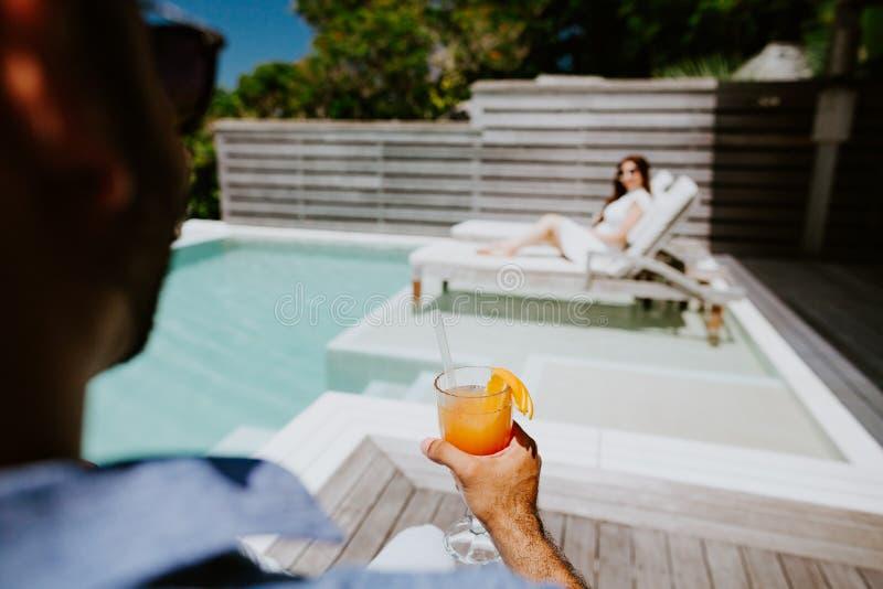 Het paar ontspant en drinkt cocktail bij de strandtoevlucht royalty-vrije stock foto's