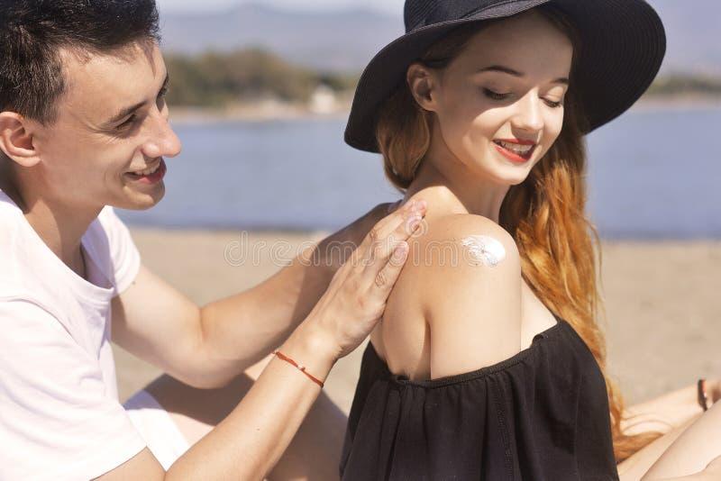 Het paar op een vakantie van het de zomerstrand heeft goede skincare met hoge spf sunblock, zonroom Paar dat suncream inschrijft stock foto
