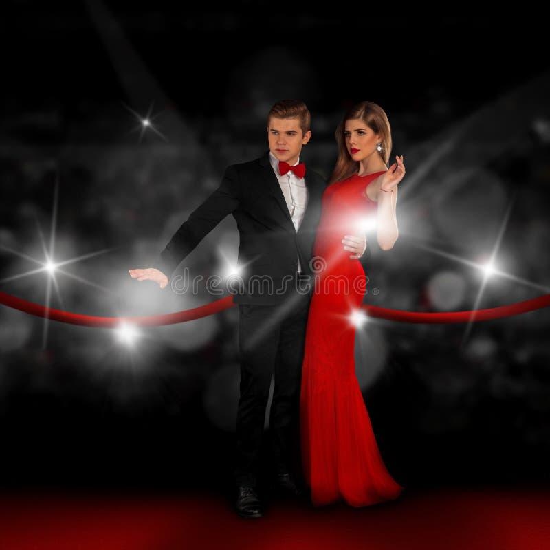 Het paar op rood tapijt stelt in paparazziflitsen royalty-vrije stock afbeeldingen
