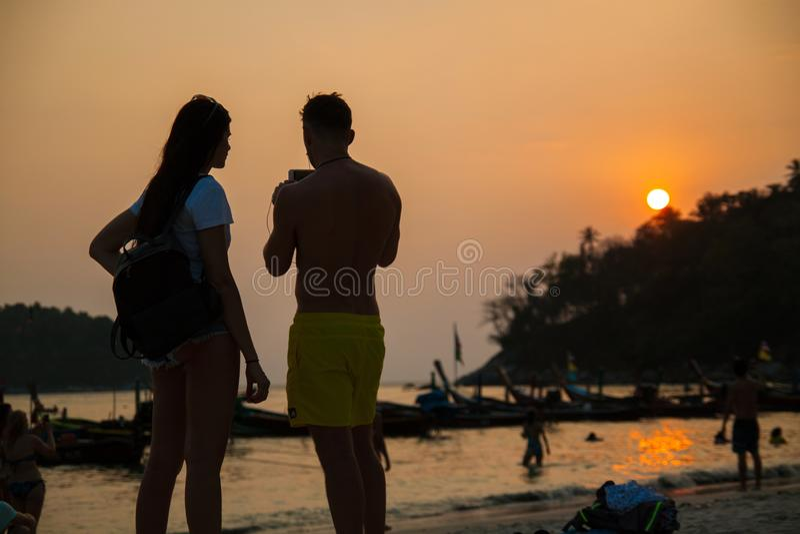 Het paar op het strand, de de zomervakantie, de Man en de Vrouw nemen Foto van Zonsondergang royalty-vrije stock afbeelding