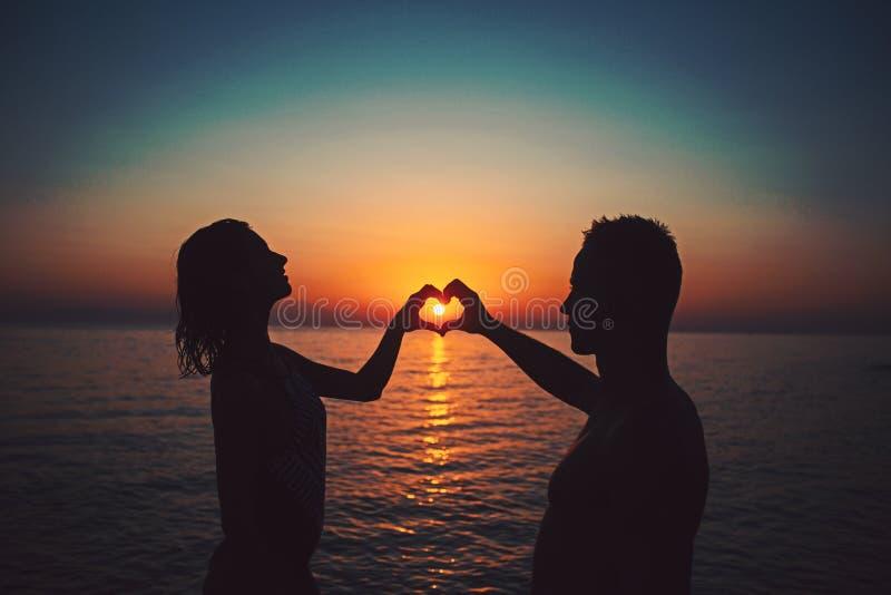 Het paar op het zonsondergangstrand bij tropische toevlucht maakt hart van het concept van de handenreis stock foto