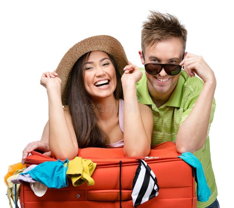Het paar pakt omhoog koffer met kleding voor het reizen in stock foto