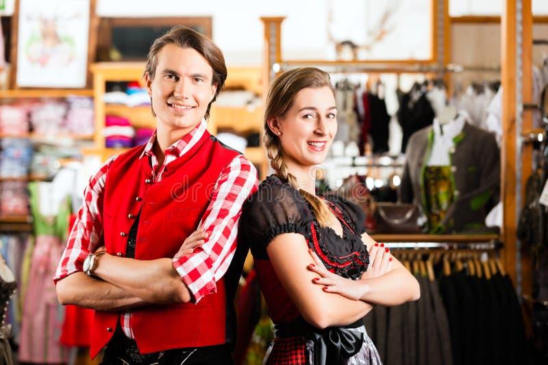 Het paar probeert Dirndl of Lederhosen in een winkel stock fotografie