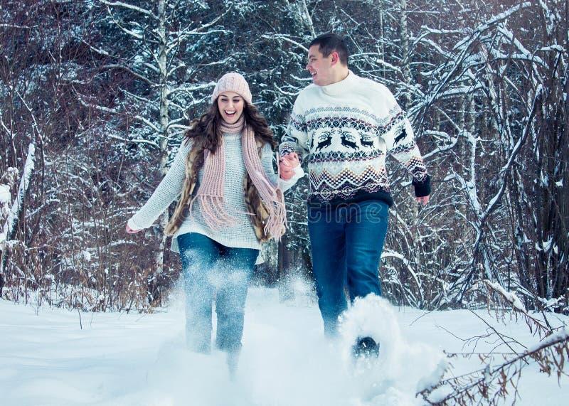Het paar stelt en werpt sneeuw in werking stock foto's