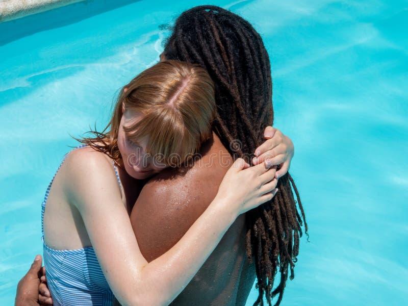 Het paar tussen verschillende rassen in liefde, koesterde status in de blauwe waterpool stock foto