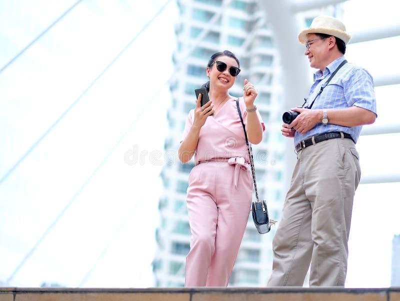 Het paar van Aziatische oude man en vrouwentoerist danst onder de grote bouw van grote stad Deze foto bevat ook concept goed stock foto's