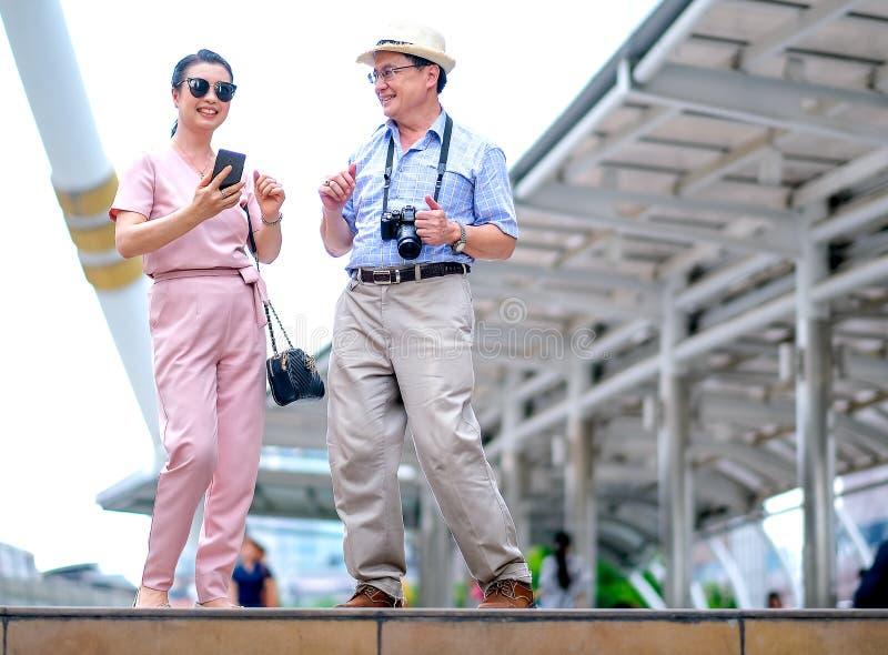 Het paar van Aziatische oude man en vrouwentoerist danst onder de grote bouw van grote stad Deze foto bevat ook concept goed royalty-vrije stock foto's