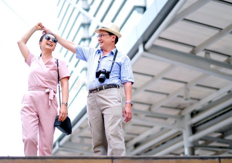 Het paar van Aziatische oude man en vrouwentoerist danst onder de grote bouw van grote stad Deze foto bevat ook concept goed stock afbeeldingen