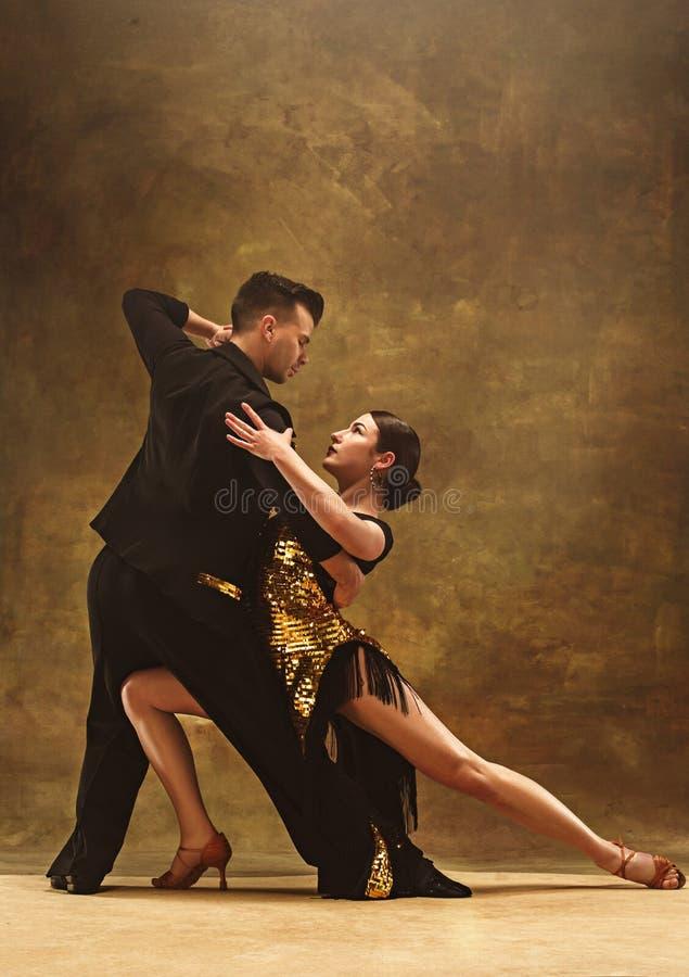 Het paar van de dansbalzaal in gouden kleding die op studioachtergrond dansen stock fotografie