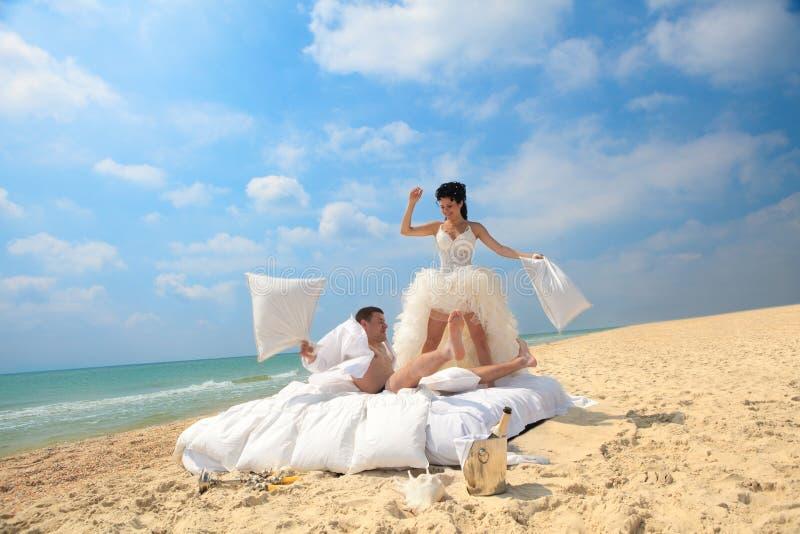 Het paar van de jonggehuwde het vechten met hoofdkussens royalty-vrije stock afbeelding