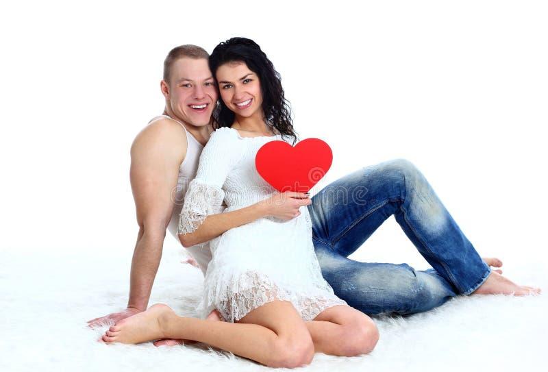 Het paar van de liefde op de vloer met een groot rood hart royalty-vrije stock fotografie