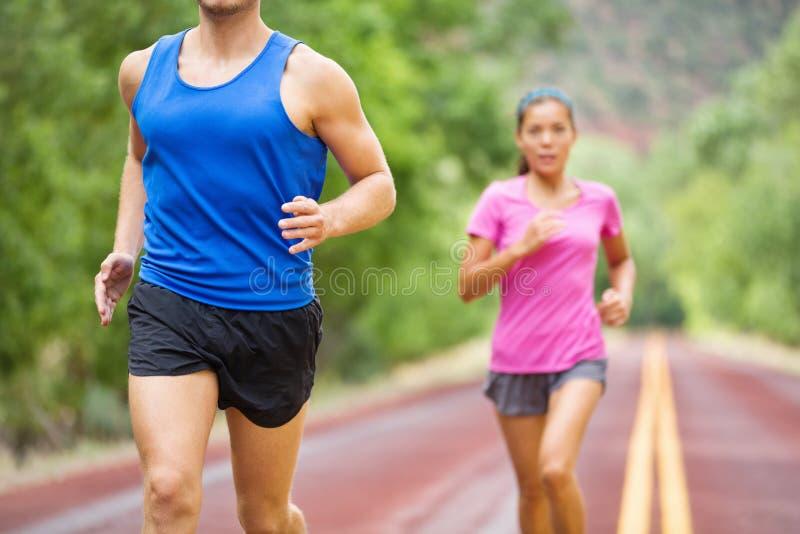 Het paar van de marathon lopende atleet opleiding op weg stock afbeeldingen