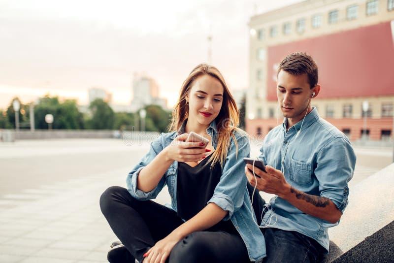 Het paar van de telefoonverslaafde kan niet zonder gadgets leven stock afbeelding