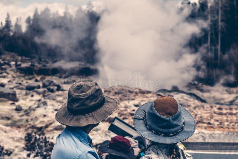 Het paar van de toeristenfamilie geniet van de mening van de geiserstoom met hun jonge geitjes in het Nationale Park van Yellowst stock fotografie