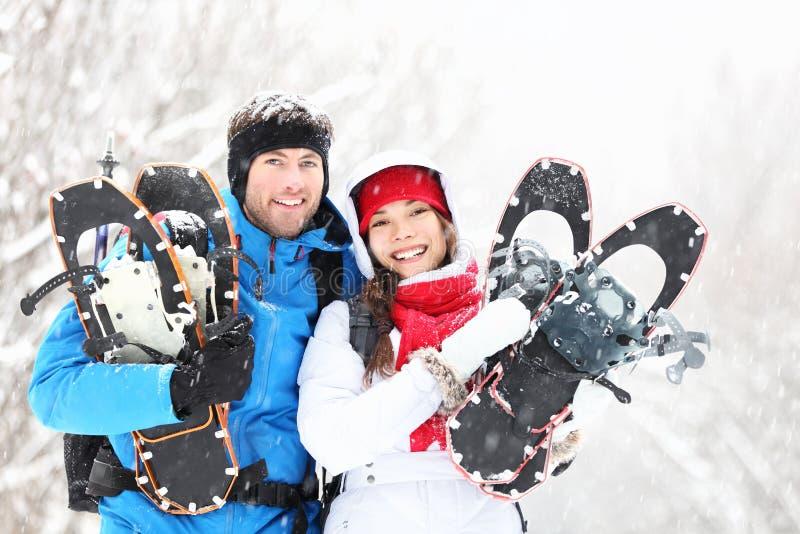 Het paar van de winter in openlucht op sneeuwschoenen stock foto's