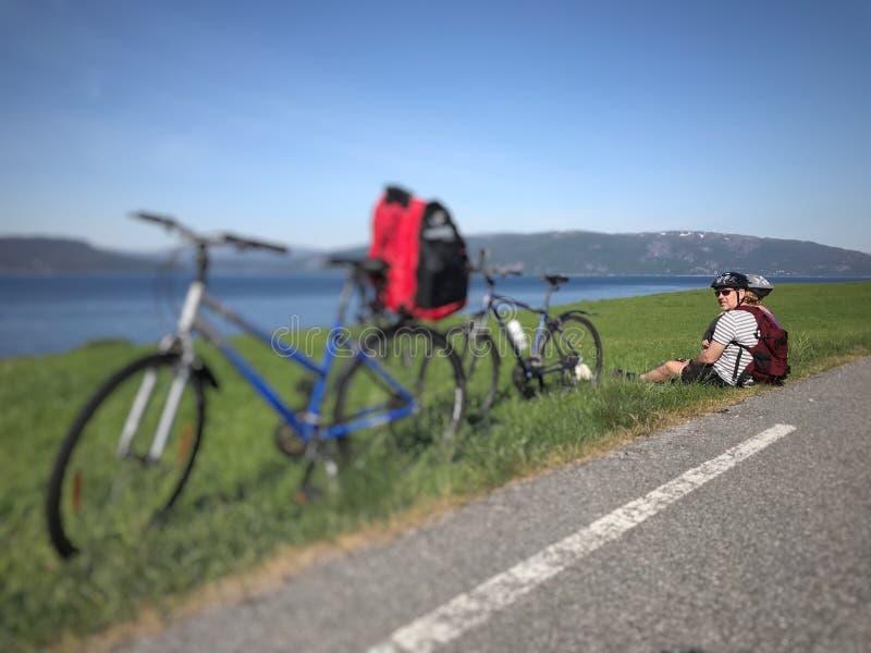 Het paar van fietsers zit op een weide stock foto's