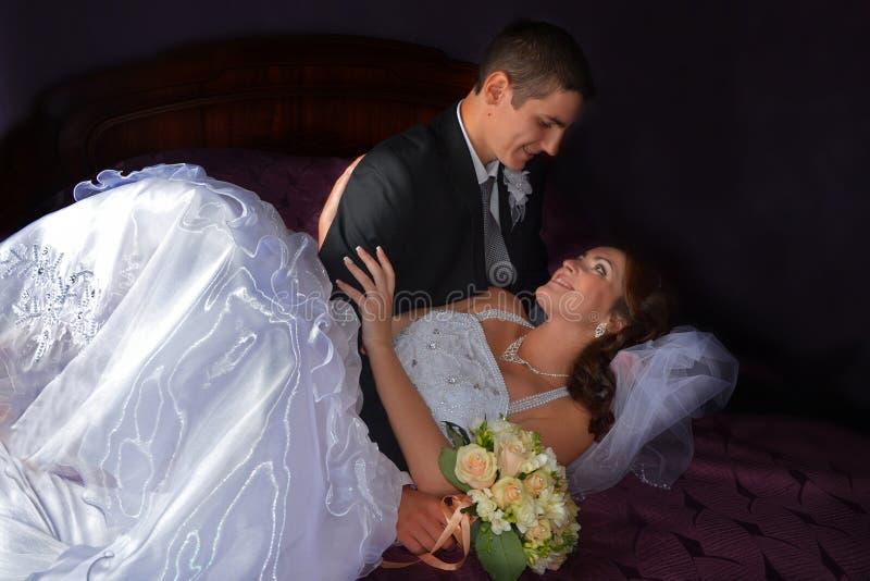 Het Paar van het huwelijk Charmante Bruid en Bruidegomzitting op een bed royalty-vrije stock afbeelding