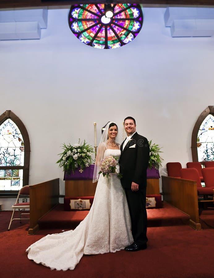 Het paar van het huwelijk in een kerk stock afbeelding