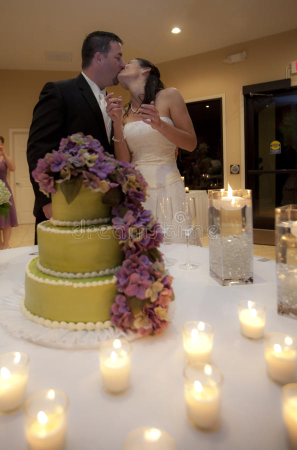 Het paar van het huwelijk het kussen door cake stock fotografie