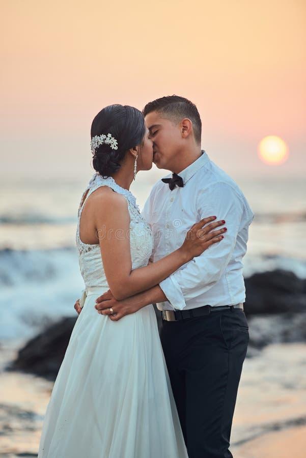 Het paar van het huwelijk het kussen op strand royalty-vrije stock afbeeldingen