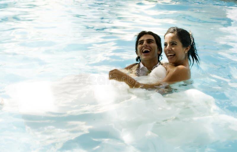Het paar van het huwelijk het zwemmen stock fotografie